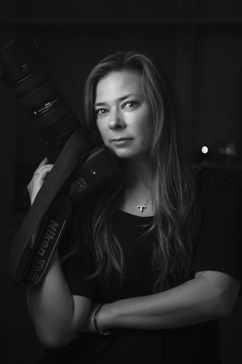 Black and White photo of Photographer Tanya Wilson standing holding up Nikon camera
