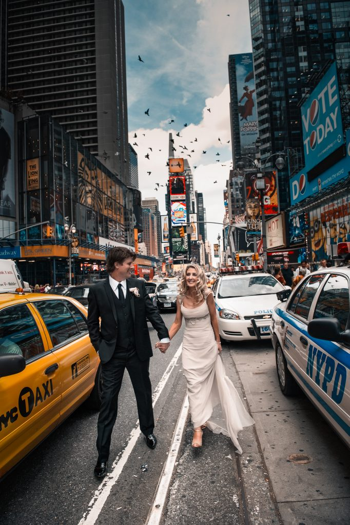 Happy wedding couple walk hand in hand through the streets of New York City between an iconic yellow can and NYPD car
