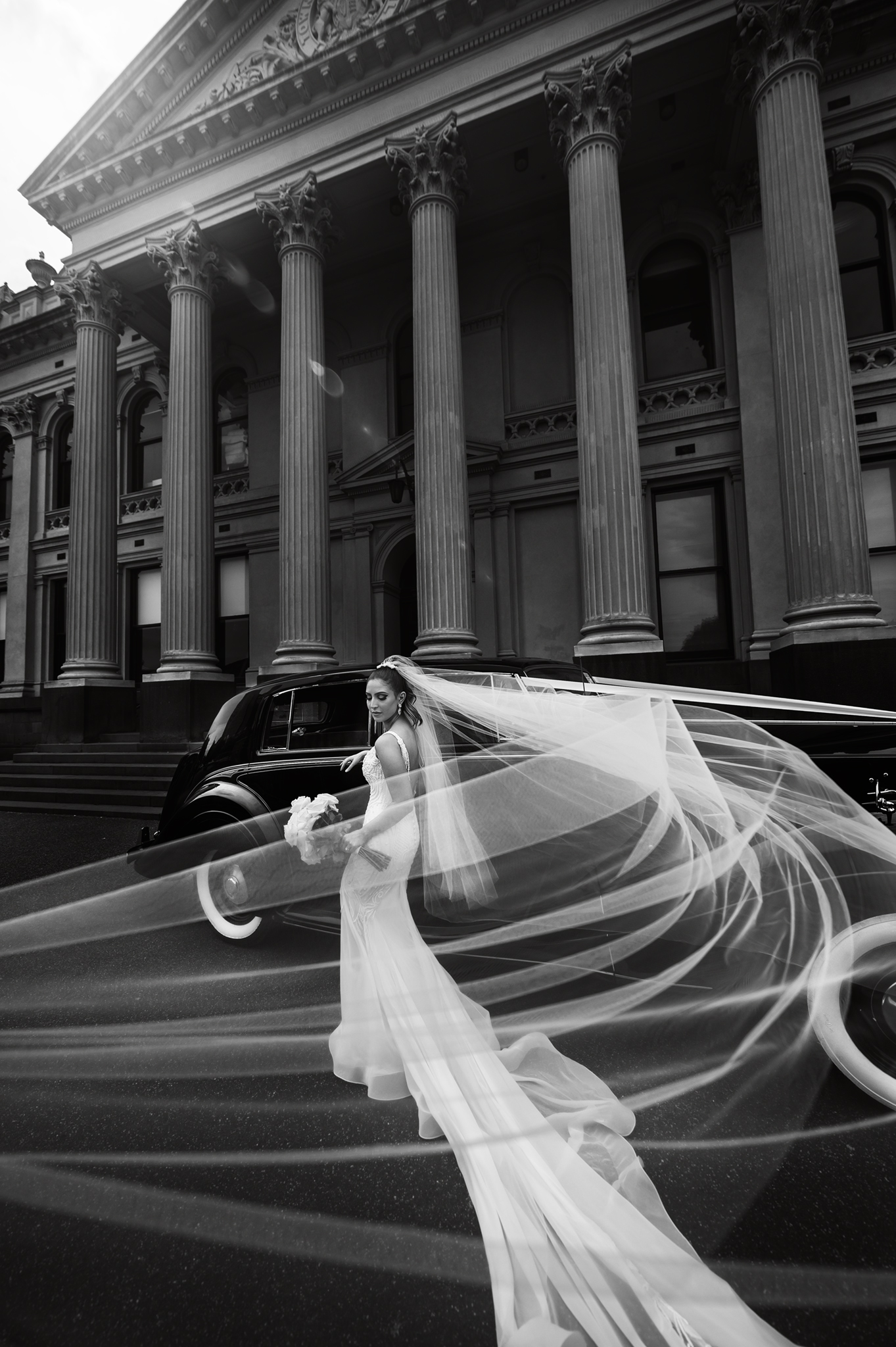 Bride standing next to black Rolls Royce with veil blowing in the wind out front of the columns of south Melbourne town hall
