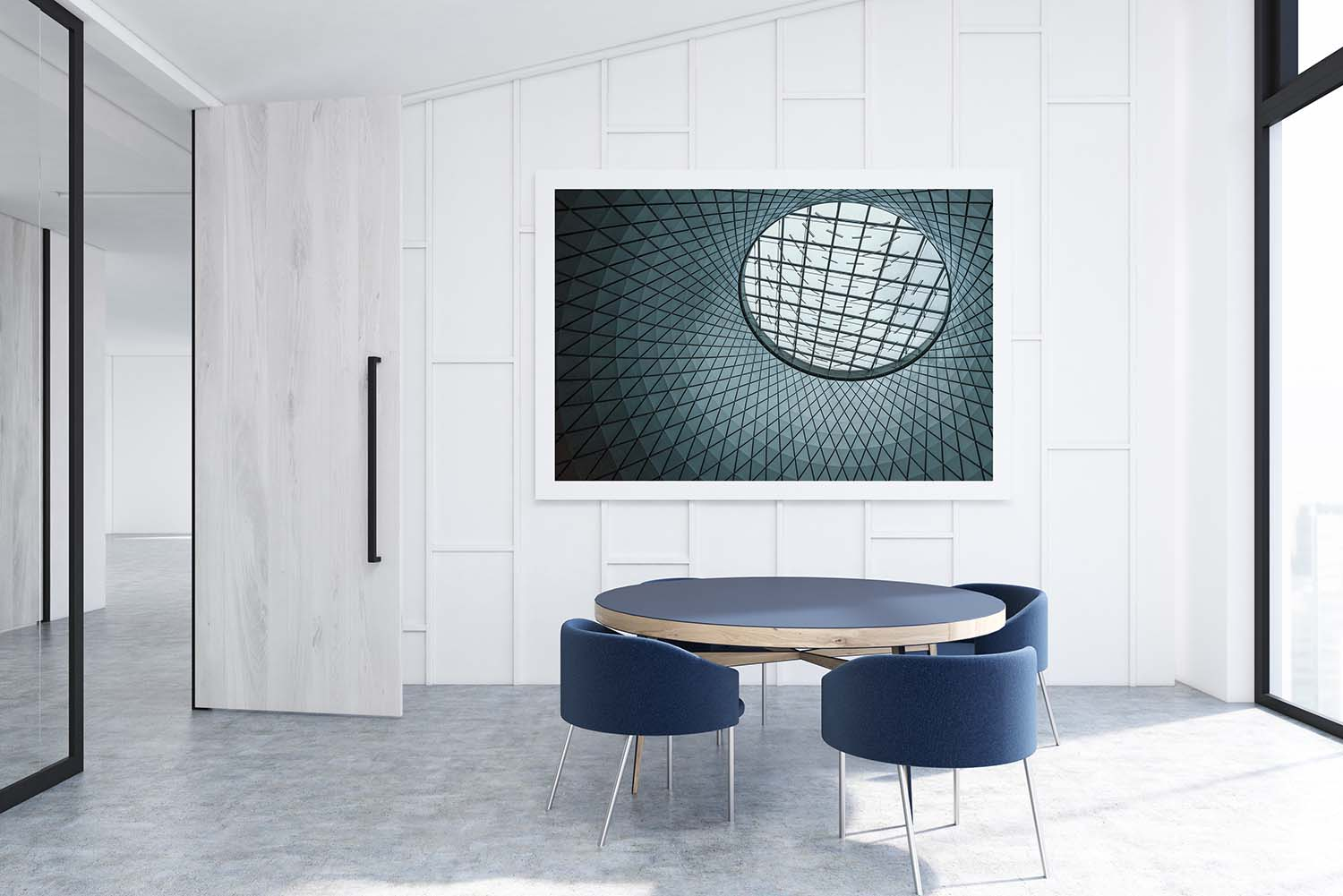 Office with white walls. Waiting area with a round table surrounded by armchairs. Horizontal poster on the wall.